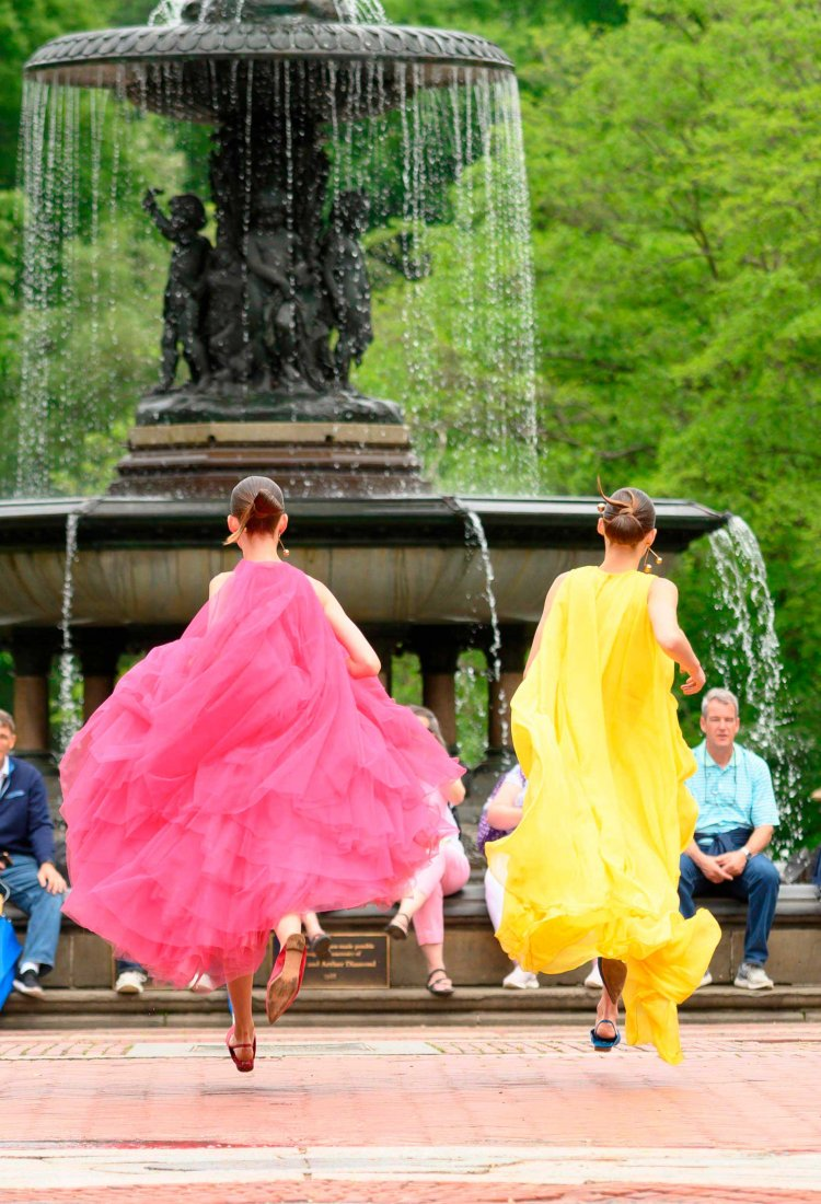 carolina herrera new york models wearing pink and yellow gowns jumping in central park
